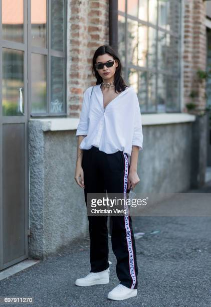 A guest wearing a white button shirt and a Givenchy jogger pants is seen outside Malibu 1992 during Milan Men's Fashion Week Spring/Summer 2018 on...