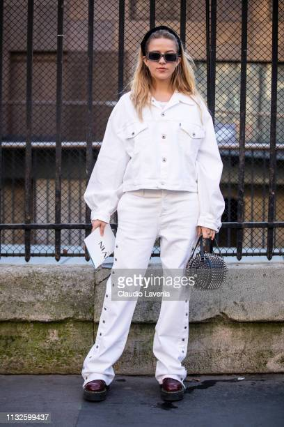 Guest, wearing a white denim jacket with matching jeans, burgundy Dr. Martens, black studded bag and black hairband, is seen outside Lanvin on Day 3...
