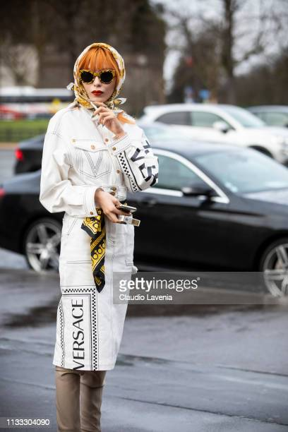 A guest wearing a white denim Versace jacket with matching Versace skirt beige boots and printed hair scarf is seen outside Haider Ackermann on Day 6...