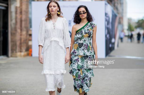 A guest wearing a white dress and a guest wearing a dress with floral print during MercedesBenz Fashion Week Resort 19 Collections at Carriageworks...