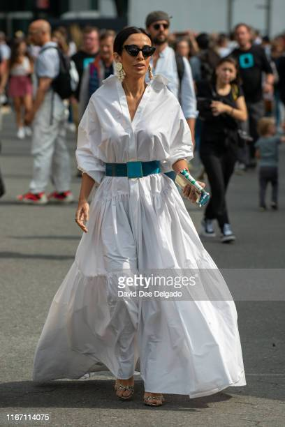 Guest wearing a white dress and teal belt attends the Carolina Herrera show during New York Fashion Week at the Garden of the Battery on September 9,...