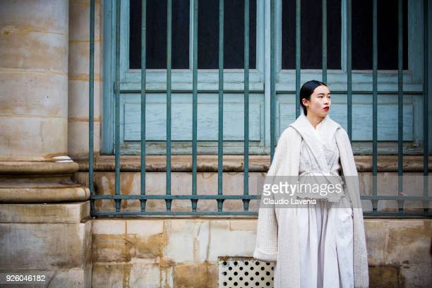 Guest wearing a white dress and white coat is seen in the streets of Paris before the Ann Demeulemeester show during Paris Fashion Week Womenswear...