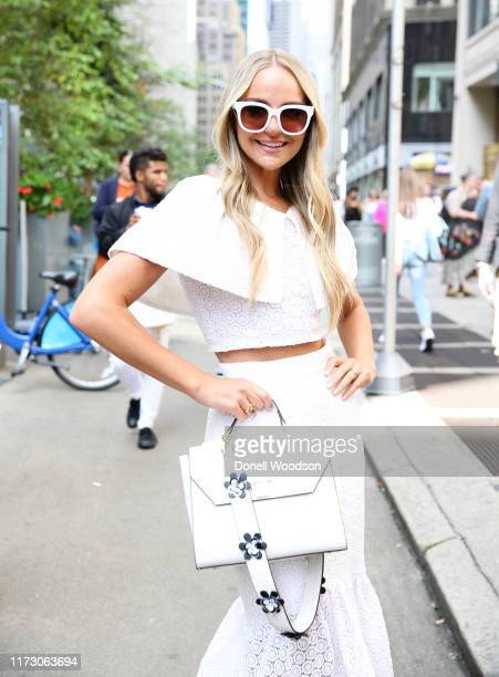 Guest wearing a white dress and white handbag with flowers during New York Fashion Week at Gotham Hall on September 07, 2019 in New York City.