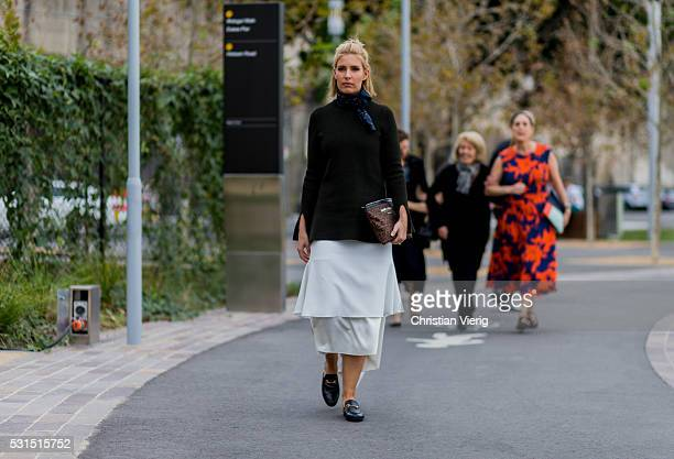 A guest wearing a white dress from Toni Maticevski a olive sweater a Saint Laurent clutch Gucci Loafers and a navy scarf outside Toni Maticevski at...