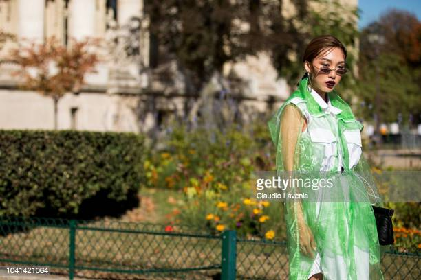 A guest wearing a white dress white ankle boots and a green seethrough trench coat is seen after the Maison Margiela show on September 26 2018 in...