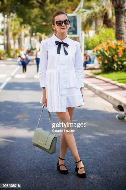 A guest wearing a white dress with black bow tie and Armani light green bag is seen in the streets of Cannes during the 71st annual Cannes Film...