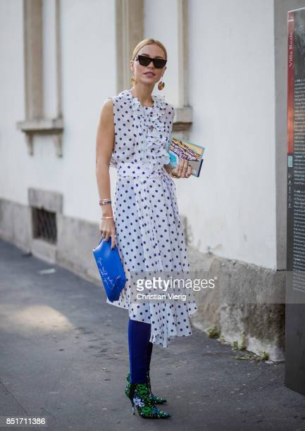 A guest wearing a white dress with dot print blue clutch is seen outside Tods during Milan Fashion Week Spring/Summer 2018 on September 22 2017 in...