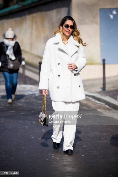 Guest wearing a white fur coat and a white pants is seen in the streets of Paris before the Dior show during Paris Fashion Week Womenswear...