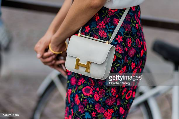 A guest wearing a white Hermes mini bag and pants with floral print during Pitti Uomo 90 on June 14 in Florence Italy