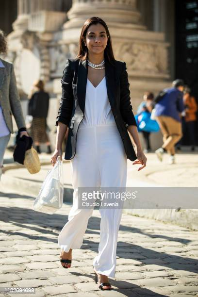 A guest wearing a white jumpsuit black sandals black blazer and seethrough bag is seen outside Maison Margiela on Day 3 Paris Fashion Week...