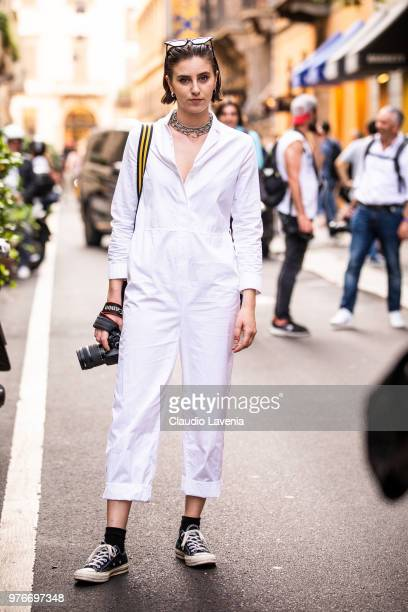 Guest wearing a white jumpsuit is seen in the streets of Milan before the Versace show during Milan Men's Fashion Week Spring/Summer 2019 on June 16...