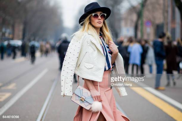 A guest wearing a white leather jacket salmon coloured skirt outside Fendi during Milan Fashion Week Fall/Winter 2017/18 on February 23 2017 in Milan...