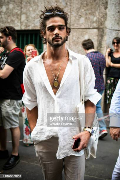 A guest wearing a white linen shirt beige pants and white canvas bag is seen outside Giorgio Armani show during the Milan Men's Fashion Week...