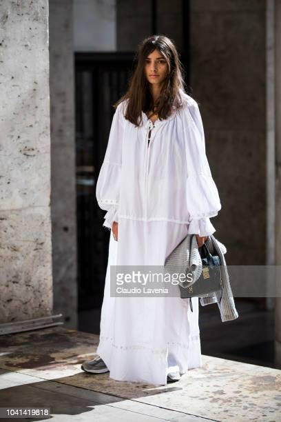 A guest wearing a white maxi dress and sneakers is seen after the Marques Almeida show on September 26 2018 in Paris France