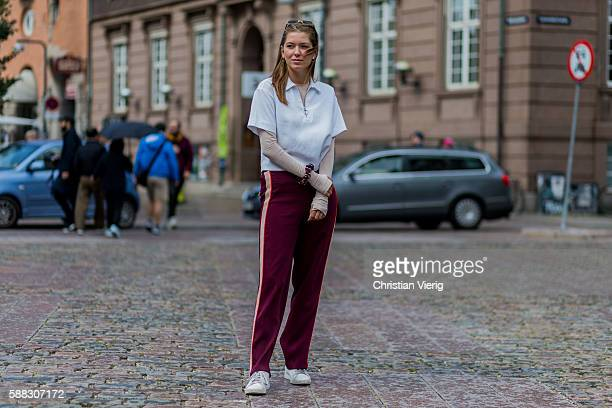 A guest wearing a white polo shirt and bordeaux track suit pants outside Nicholas Nybro during the first day of the Copenhagen Fashion Week...