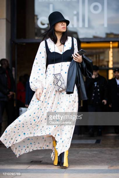A guest wearing a white printed maxi dress black crop top black hat and yellow and black boots is seen outside Haider Ackermann during Paris Fashion...