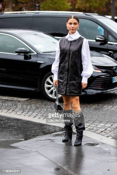 Guest, wearing a white shirt, black leather mini dress, black boots and black bag, is seen outside the Chanel show during Paris Fashion Week -...