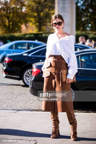 A guest wearing a white shirt brown midi leather skirt snake print boots and snake print bag is seen before the Rochas show on September 26 2018 in...