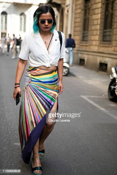 Guest, wearing a white shirt, colorful striped long skirt and metallic green sandals, is seen outside Giorgio Armani show, during the Milan Men's...