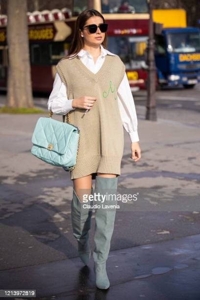 Guest, wearing a white shirt, long beige knitted vest, teal Chanel bag and teal over the knees boots, is seen outside Chanel, during Paris Fashion...