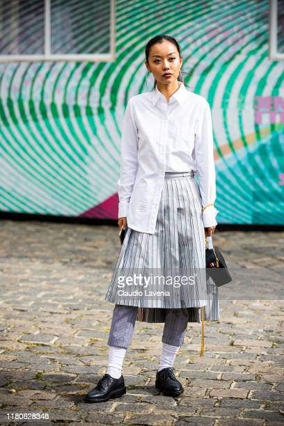 A guest wearing a white shirt striped skirt checked pants and black shoes is seen outside the Thom Browne show during Paris Fashion Week Womenswear...