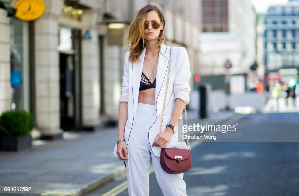 A guest wearing a white suit and bra during the London Fashion Week Men's June 2017 collections on June 10 2017 in London England