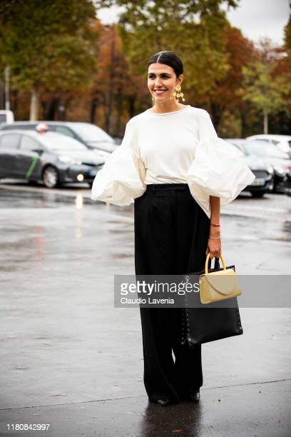 A guest wearing a white top black pants black tote bag and yellow small bag is seen outside the Chanel show during Paris Fashion Week Womenswear...