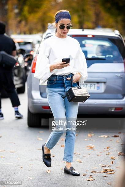 Guest, wearing a white top, blue jeans, black loafers and black bag, is seen outside the Elie Saab show during Paris Fashion Week - Womenswear Spring...