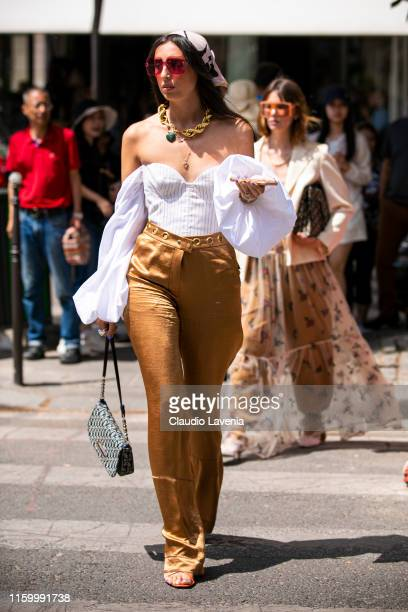 A guest wearing a white top bronze pants Dior bag orange heels and printed hair scarf is seen outside Christian Dior show during Paris Fashion Week...