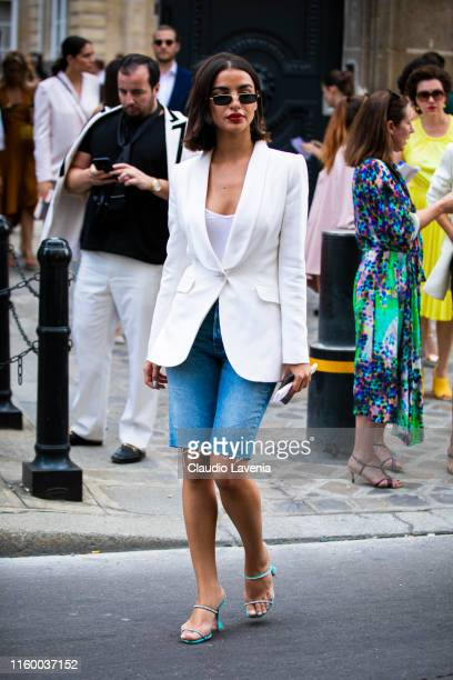 A guest wearing a white top white blazer denim biker shorts and light blue sandals is seen outside Ralph and Russo show during Paris Fashion Week...