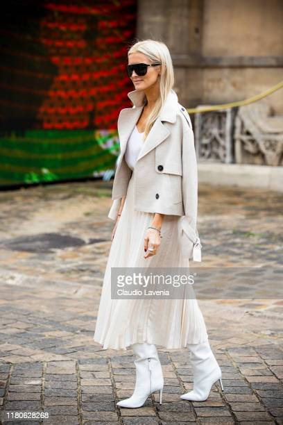 Guest, wearing a white top, white midi skirt, cream jacket and white boots, is seen outside the Thom Browne show during Paris Fashion Week -...