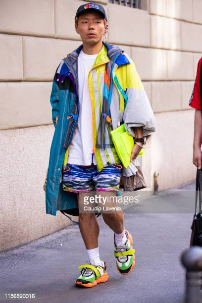 Guest, wearing a white t-shirt, colorful shorts, colorful maxi jacket, Etro hat and colorful sneakers, is seen outside Giorgio Armani show, during...