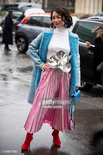 A guest wearing a white turtleneck sweater pink and silver long skirt with silver big belt red boots blue bag and light blue fur coat is seen outside...