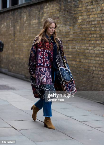 A guest wearing a wool coat denim jeans outside Mulberry on day 3 of the London Fashion Week February 2017 collections on February 19 2017 in London...