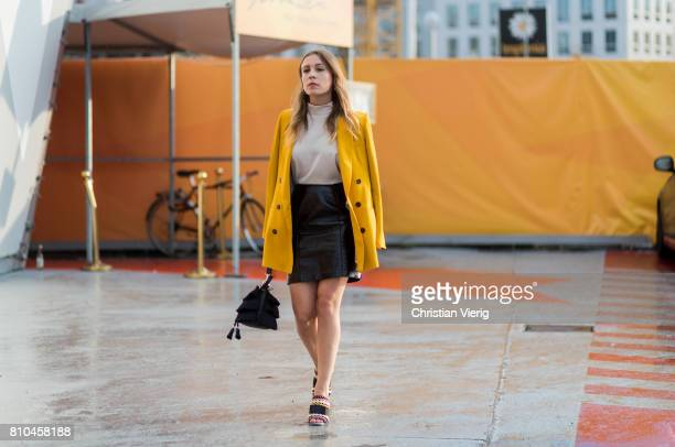 A guest wearing a yellow coat black skirt bag outside Marina Hoermanseder during the MercedesBenz Fashion Week Berlin Spring/Summer 2018 on July 7...