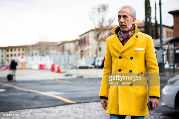 A guest wearing a yellow coat is seen during the 93 Pitti Immagine Uomo at Fortezza Da Basso on January 11 2018 in Florence Italy