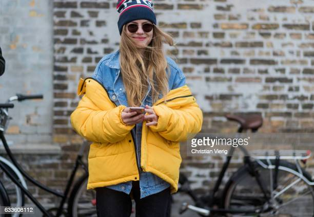 A guest wearing a yellow down feather jacket denim jacket beanie outside Munthe during the Copenhagen Fashion Week Autumn/Winter 17 on February 2...