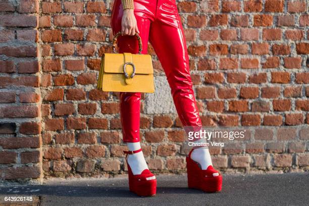 A guest wearing a yellow Gucci bag red latex pants outside Gucci on February 22 2017 in Milan Italy