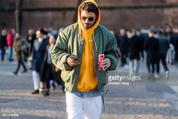 A guest wearing a yellow hoody olive green bomber jacket white pants with a Coca Cola can on January 10 2017 in Florence Italy