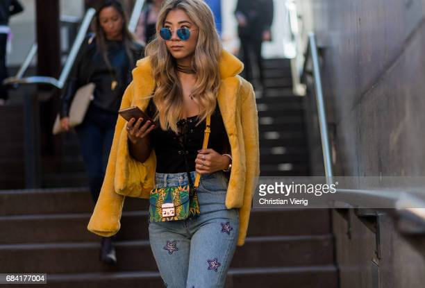 A guest wearing a yellow jacket Furla bag at day 4 during MercedesBenz Fashion Week Resort 18 Collections at Carriageworks on May 17 2017 in Sydney...