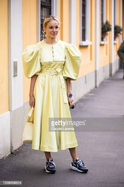 Guest, wearing a yellow maxi dress, yellow bag and Nike sneakers, is seen outside Tod's show, during Milan Fashion Week Fall/Winter 2020-2021 on...