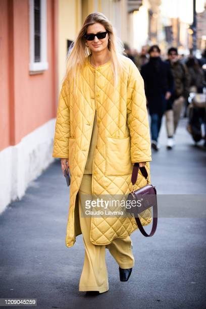 Guest, wearing a yellow pants, yellow long jacket and burgundy bag, is seen outside Tod's show, during Milan Fashion Week Fall/Winter 2020-2021 on...