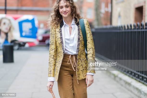 A guest wearing a yellow snakeskin jacket outside Anya Hindmarch on day 3 of the London Fashion Week February 2017 collections on February 19 2017 in...