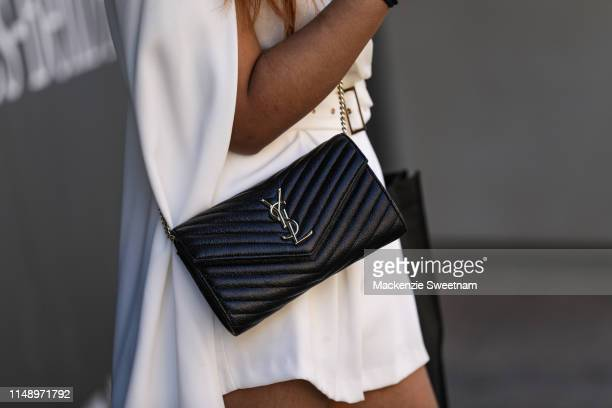 A guest wearing a YSL purse at MercedesBenz Fashion Week Resort 20 Collections on May 14 2019 in Sydney Australia