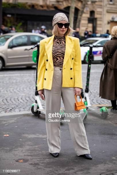 A guest wearing a zebra print top beige pants yellow blazer black heels orange Jacquemus bag and snake print hair scarf is seen outside Altuzarra on...