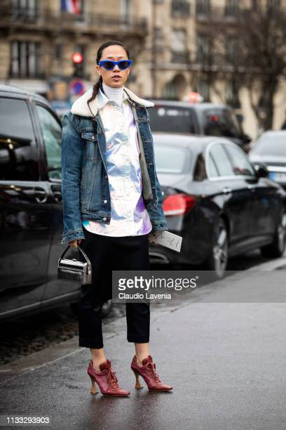 Guest, wearing an holographic shirt, black pants, red heels, silver bag and denim jacket, is seen outside Haider Ackermann on Day 6 Paris Fashion...