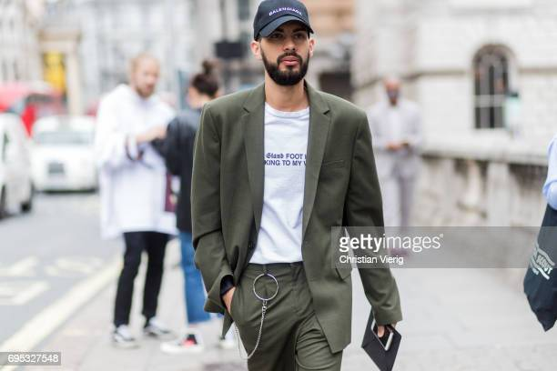 A guest wearing an olive suit and Balenciaga cap during the London Fashion Week Men's June 2017 collections on June 12 2017 in London England