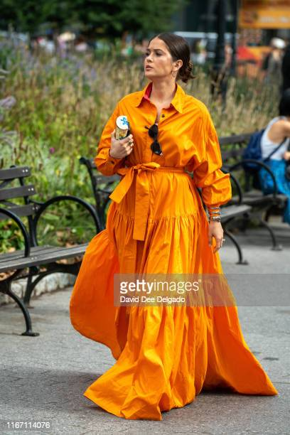 A guest wearing an orange dress attends the Carolina Herrera show during New York Fashion Week at the Garden of the Battery on September 9 2019 in...