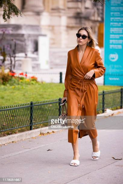 Guest, wearing an orange leather coat, white Bottega Veneta sandals and beige bag, is seen outside the Chloe show during Paris Fashion Week -...