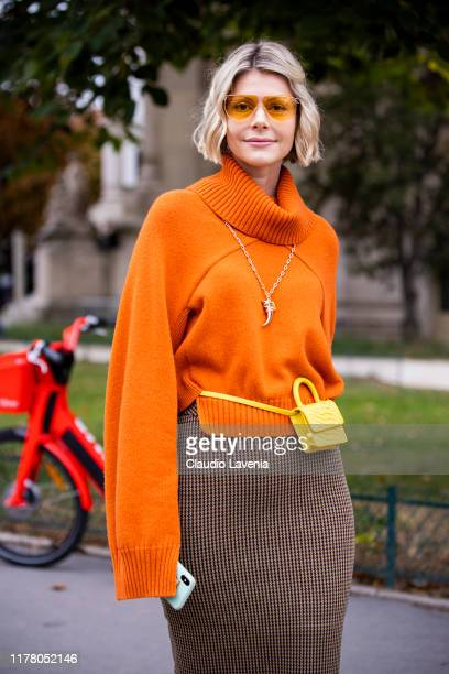 Guest, wearing an orange sweater, checked midi skirt and yellow mini belt bag, is seen outside the Chloe show during Paris Fashion Week - Womenswear...